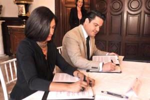 Lorena Cruz Sánchez y Aristóteles Sandoval Díaz firmando un documento
