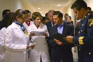 Mercedes Juan y Enrique Peña Nieto revisan un documento al lado de un grupo de guncionarios