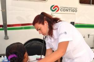 Doctora revisando a paciente enfrente de la unidad medica móvil