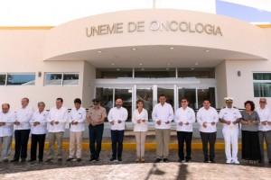 Funcionarios de pie cortando listón en la fachada de la UNEME en Oncología