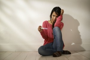 Sad Asian girl looking at pregnancy test sitting on floor
