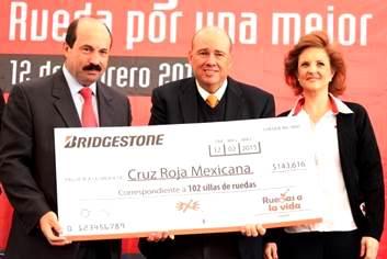 Funcionarios sosteniendo un cheque grande para la Cruz Roja