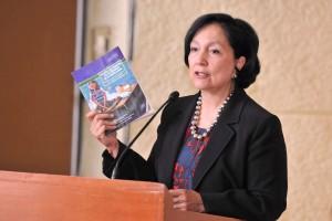 """Amalia Dolores García Medina sostiene en su mano el libro """"Mujeres que transitan en los márgenes de un mundo global"""""""