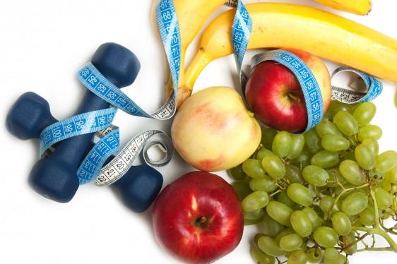Frutas, cinta métrica y pesas para ejercicio