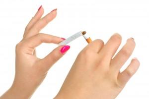 Manos de una mujer rompiendo un cigarro
