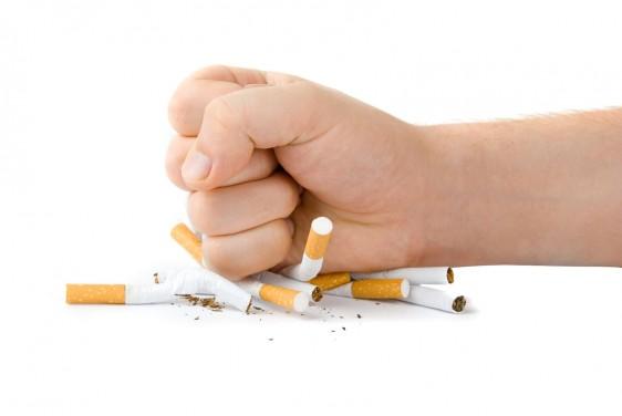 Mano aplastando cigarros
