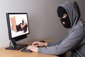 Hombre con mascara observando una pantalla de computadora con una imagen intima
