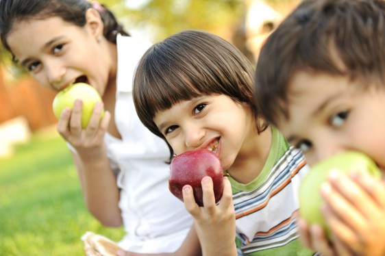 Grupo de niños comiendo manzanas en un parque