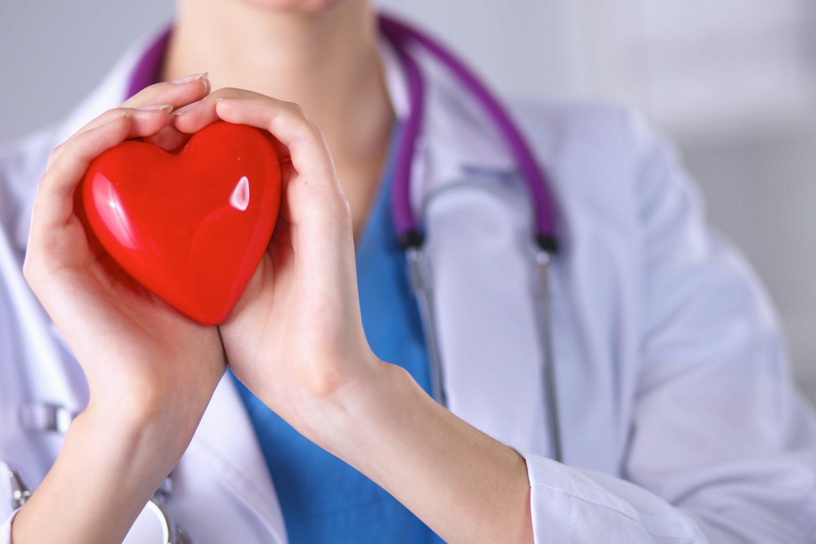 Doctora sostiene una figura con forma de corazón rjo en sus manos
