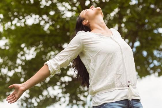 Mujer con brazos abiertos y mirando hacia un cielo azul al fondo arboles