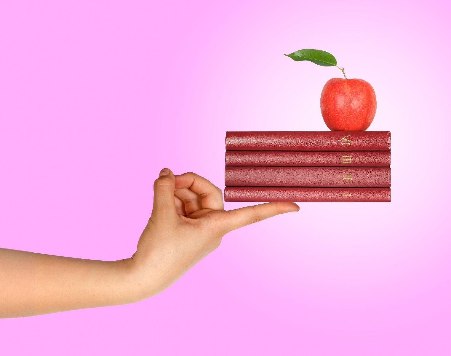 Mujer sosteniendo libros con una manzana