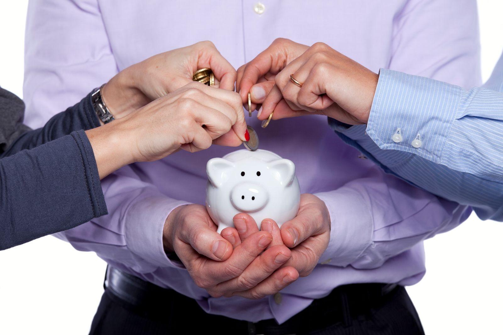 Personas depositando una moneda en una alcacía en forma de cochinito