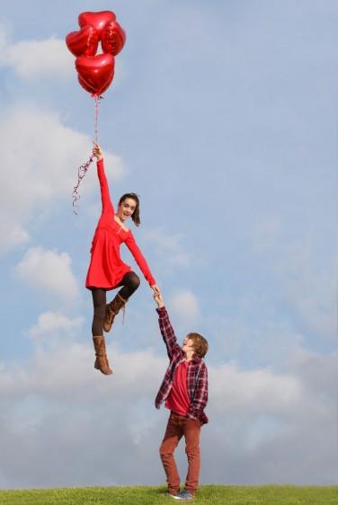 Adolescente con globos y despegando agarrada de la mano de su novio