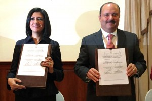 Lorena Cruz Sánchez y César Duarte Jáquez sosteniendo un documento con firmas