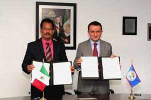 De izquierda a derecha Pablo Marín y Mikel Arriola sotienen un documento al lado de las banderas de México y Belice y al fondo la fotografía de Enrique Peña Nieto con la banda presidencial de México