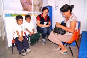 Servidora pública llenando formulario con dos niños y su madre