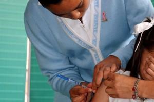 Enfermera aplicando vacuna a una niña