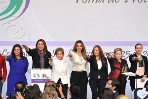 Mujeres de la agrupación levantan la mano para hacer su juramento.