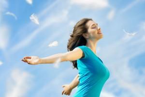Mujer con los brazos abiertos y ojos cerrados respirando en un cielo azul