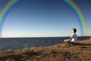 Mujer mirando al mar con un arco iris
