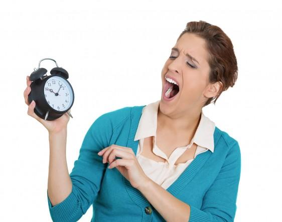 Mujer bostezando con reloj en la mano marca las 10:10