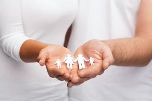 Una pareja con camisas blancas sostiene en las manos un recorte de papel que representa una famila familia
