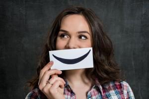Mujer con una hoja de papel en su boca con una sonrisa