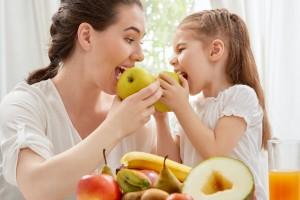 Madre e hija comiendo frutas