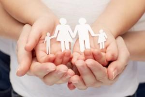 Acercamiento a las manos de una mujer y una nila que sostienen un recorte de papel con la forma de una familia