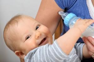 Bebé sonriendo en los brazos de una mujer agarrando un biberón