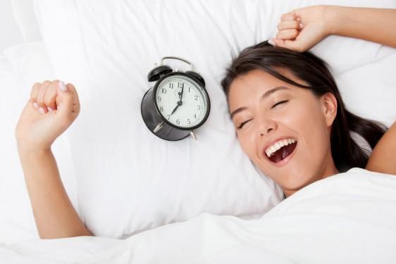 Mujer despertando con un reloj al lado de su almohada