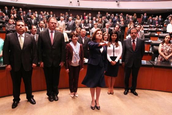Arely Gómez González levantando el brazo para rendir protesta ante la Mesa Directiva del Senado.