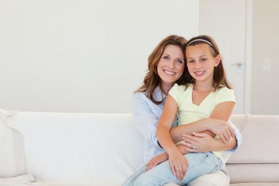 Hija sentada en las piernas de su madre en un sofá blanco