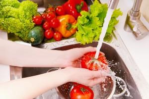 Acercamiento a las manos de una mujer lavanado con agua verduras