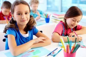 Niñla sonriendo en un salón de clases