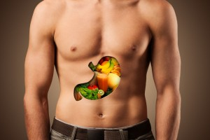 Acercamiento a pecho de un hombre con recorte en forma de estomago conteniendo frutas y verduras