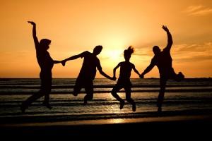 Grupo de hombres y mujeres saltando en un amanecer naranja