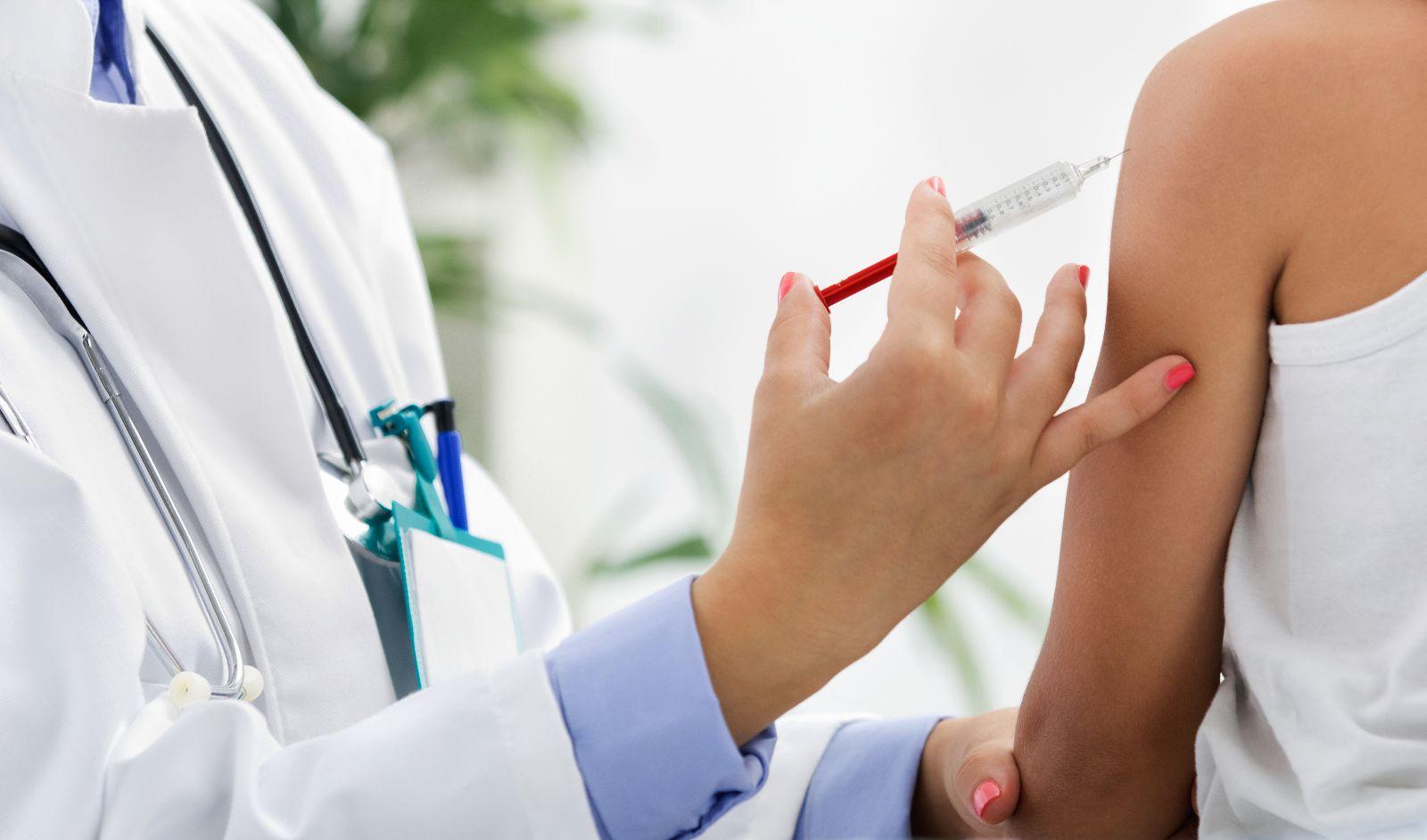 Médica aplicando una vacuna a un paciente