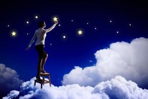 Mujer subiendo una escalera para alcanzar una estrella en un escenario con nubes y estrellas