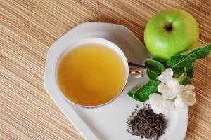 Taza con té Verde y una manzana al lado