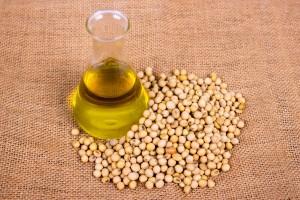 Envase con aceite de soya sobre una mantel con semillas de soya