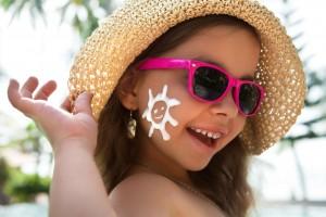 Niña con sombrero y lentes sonriendo con protector solar aplicado en la mejilla con la forma de un sol
