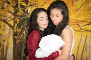 Pareja de mujeres abrazando a un bebe
