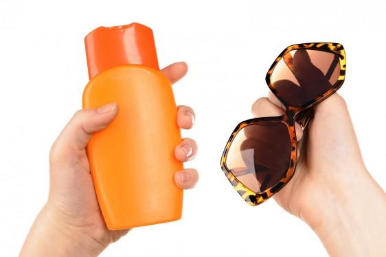 Mujer sosteniendo crema de bloqueador solar y lentes de sol