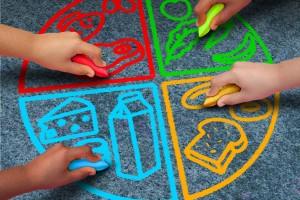 Niños dibujando los cuatro grupos de alimentos con gis en una calle