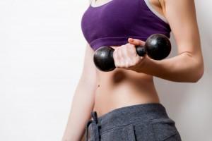 Mujer soseniendo unas pesas en sus manos