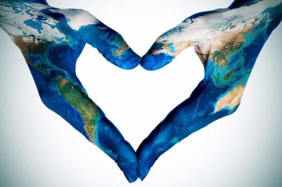 Manos con maquillaje de mundo haciendo la forma de un corazón