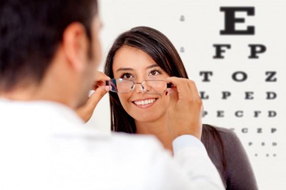 Doctor colocado gafas a una mujer