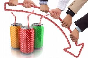 Manos sosteniendo una flecha hacia abajo con latas de refresco