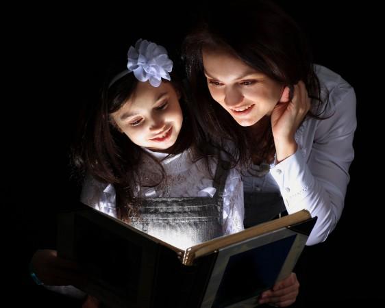 Madre e hia leyendo en un libro que emite una luz